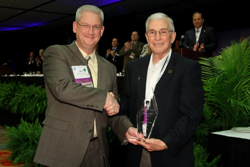 Don Bush is presented with the Volunteer of the Year Award by President Dave Hawn in 2009 for all his years of work on the RRC Exam Development Subcommittee.
